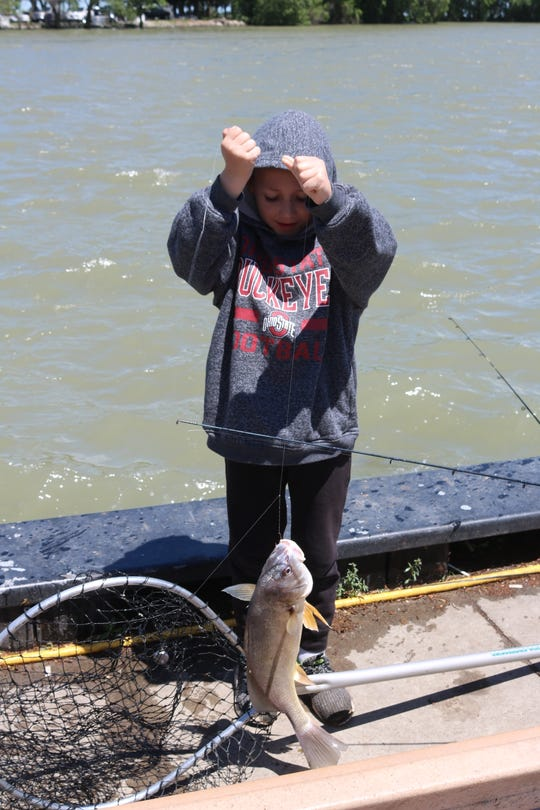 Jackson Koloff removes a sheephead from the net that had just been reeled in by his brother, Anthony, during a trip to downtown Port Clinton on Saturday.