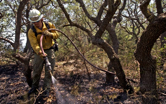 Joshua Torres douses a hotspot on the Arroyo Grande Fire burning near Sonora on Saturday, June 13, 2020.