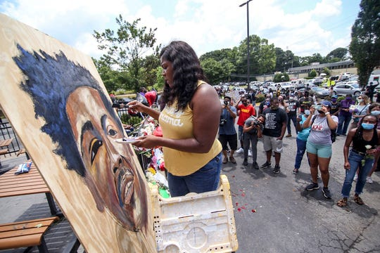 Ashley Dopson paints a picture of Rayshard Brooks in the parking lot of the Wendy's in Atlanta.