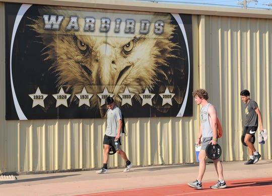 Abilene High football players carry their belongings, including a 35-pound weight, to the next workout station Monday on campus during a strength and conditioning session.