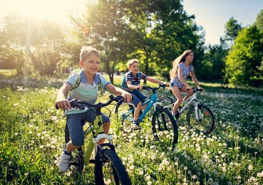 Kids ride their bikes through a field