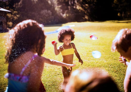 Kids throwing water balloons at each other in a back yard.