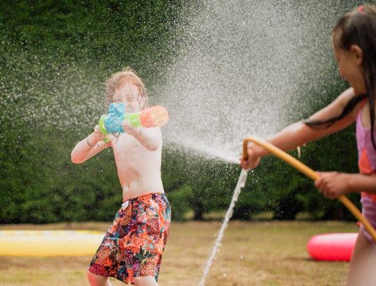 Children play in a water fight in a backyard.