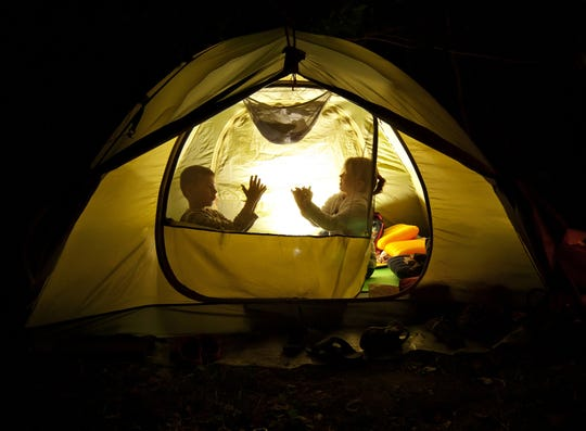 Children play in a tent while camping in their backyard