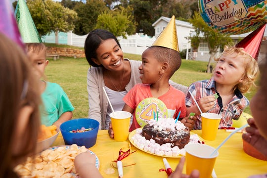 A mother enjoys an outdoor birthday party with her four year-old.