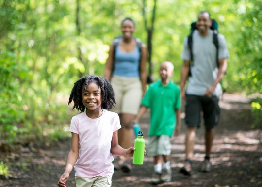 A family of four hikes in the woods.