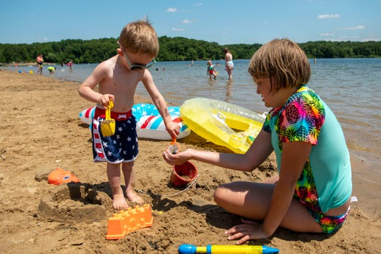 JoAnna Noel, 11, helps her one-year-old cousin Cade Rasmussen build a sandcastle on Monday, June 15, 2020 at Eagle Lake Beach in Augusta, Mich.