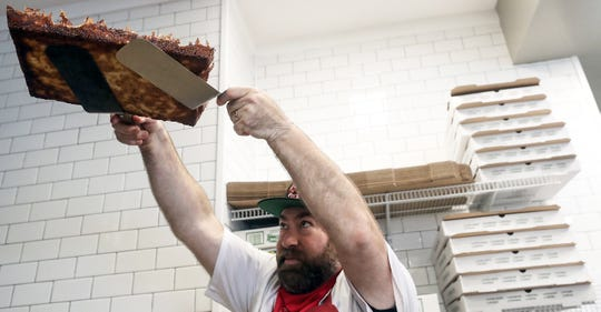 Will Grant checks the crispness of the bottom of one of his pizzas at the newly opened Sourdough Willy's Pizzeria in Kingston on Monday, June 15, 2020.