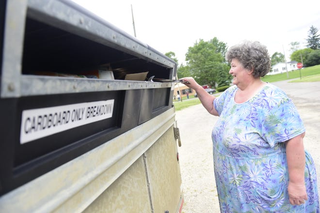 """Kathy Pinyerd pushes some crumbled cardboard into the recycling trailer in Galion East Park on Monday. It was the first time she'd recycled since the COVID-19 pandemic hit Crawford County. """"Probably three months,"""" she said, """"our whole basement was full of recyclables."""" The recycling trailers have returned to six locations countywide Monday through Friday."""