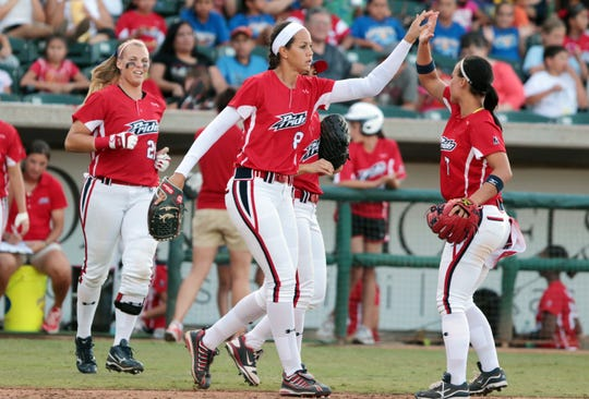 USSSA Pride Pitcher Cat Osterman (center) high-fives teammate Jenn Salling in 2012 during their game against the Akron Racers in the Hurricane Alley Coastal Classic at Whataburger Field in Corpus Christi.