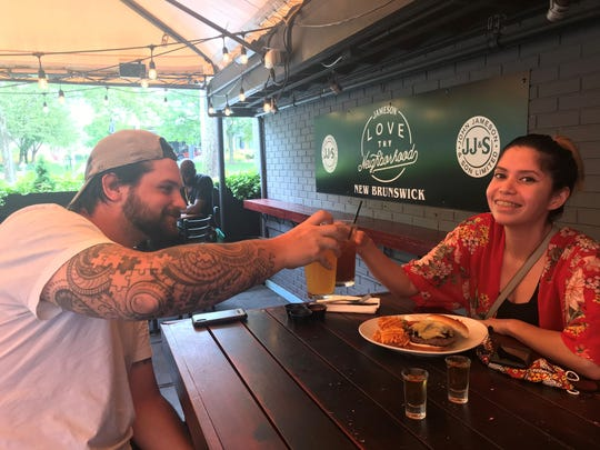 Peter Gulick and Stephanie Jimenez of Franklin Township  toast to being able to dine out again on June 15 on the patio at Blackthorn in New Brunswick.