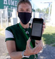 Athletic trainer for Birmingham Groves high school shows the app the players use to answer questions before practice. The school held their first workouts under the new COVID-19 guidelines Monday, June 15, 2020 at the school in Birmingham.