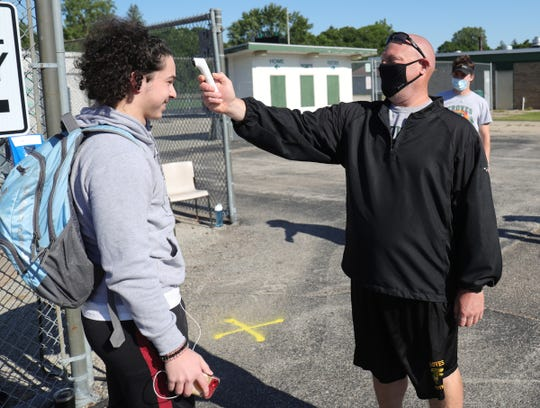 Receiver Zak Merabi has his temperature checked by line coach Mike Salter after answering questions on his phone before practice. Birmingham Groves high school held their first workouts under the new COVID-19 guidelines Monday, June 15, 2020 at the school in Birmingham.