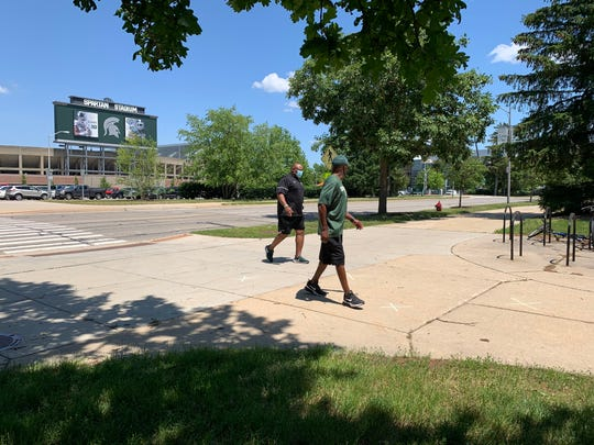 Michigan State assistant football coach Ron Burton, left, and another staff member arrive to the Smith Center for COVID-19 testing Monday.