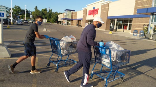 George Hall and his son, Cameron Hall, of West Bloomfield take shopping carts full of bottles and cans into the Meijer store on Haggerty Road in Commerce Township early on June 15, 2020.