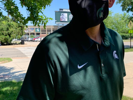 A Michigan State staff member models the face masks the athletic department is giving to athletes after they returned to campus to prepare to begin voluntary workouts.