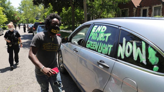 DPD officers look on as activist Tristan Taylor tries to give instructions to protesters during a drive by protest against expanding the use of facial recognition and surveillance of residents held by Detroit Will Breath Monday, June 15, 2020. The protesters drove by the home of Detroit City Councilman Andre Spivey on Detroit's East side.