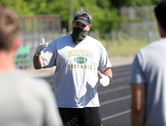 Birmingham Groves head coach Brendan Flaherty talks to players during drills. Groves held their first workouts under the new COVID-19 guidelines Monday, June 15, 2020 at the school in Birmingham.
