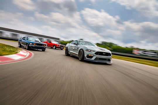 The 2021 Ford Mustang Mach 1 (fore) builds on the heritage begun by the original 1969 Mach 1 (blue and red in back).