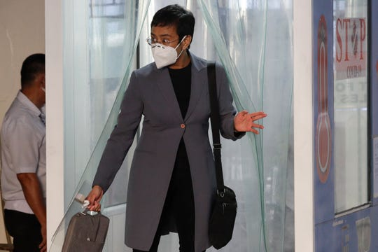 Rappler CEO and Executive Editor Maria Ressa, wearing a protective mask, exits a disinfection area before attending a court hearing Monday at Manila Regional Trial Court, Philippines. Ressa's verdict is expected to be announced Monday for a cyber libel case.