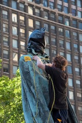 A demonstrator wraps a rope over the head of a statue of Alexander Macomb on Washington Blvd. during a march through downtown Detroit, June 14, 2020 to protest racism, police brutality, and the death of George Floyd.