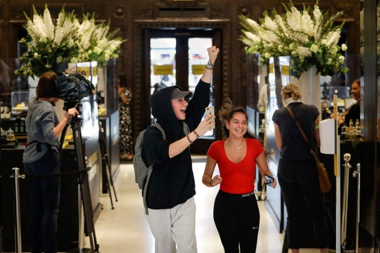 Customers cheer as they are allowed in the Selfridges department store in London, Monday. After three months of being closed under coronavirus restrictions, shops selling fashion, toys and other non-essential goods are being allowed to reopen across England for the first time since the country went into lockdown in March.