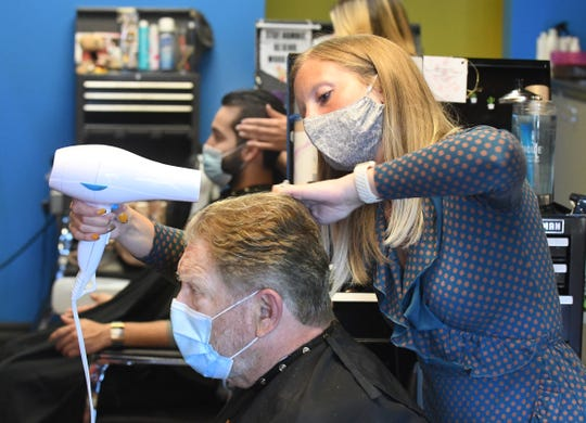 Molly Tacey styles Greg Schnaidt's locks at Lady Jane's Haircuts for Men in Troy. Masks are among personal protection equipment that have leaped from irrelevant to irreplaceable.