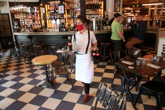 A waitress brings drinks to customers in a restaurant, Monday in Paris. Paris is rediscovering itself, and its joie de vivre, as its cafes and restaurants reopen for the first time since the fast-spreading virus forced them to close their doors March 14.