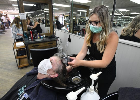 Arta Qelemeni washes Vickie Straitz's hair during her appointment at New You Salon in Birmingham on Monday.