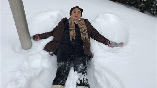 Marion Ginopolis, superintendent of Lake Orion Community Schools, makes snow angels as part of her snow day announcement last winter.