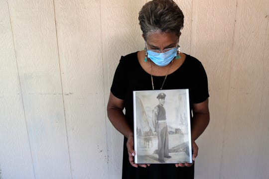 Belvin Jefferson White poses with a portrait of her father, Saymon Jefferson, at Saymon's home in Baton Rouge, La. Belvin recently lost both her father and her uncle, Willie Lee Jefferson, to COVID-19.
