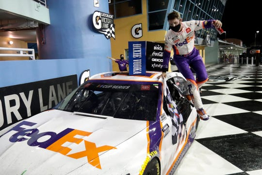 Denny Hamlin jumps from his car after winning a NASCAR Cup Series auto race Sunday in Homestead, Fla.