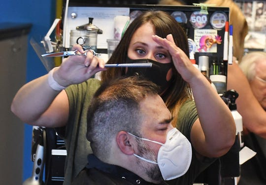 Stylist Maegan Bates gives Ben Brady a haircut at Lady Jane's Haircuts for Men in Troy on Monday.