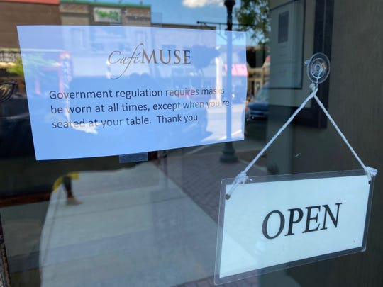A sign outside Cafe Muse in Royal Oak reminds guests that masks are required except when seated.