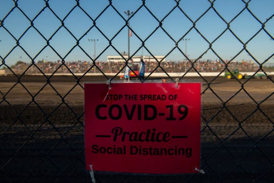 A sign offers guidance on how to keep social distancing at Tri-State Raceway in Haubstadt, Ind., June 14, 2020. Opening night was supposed to have been April 18, but this was the first race of the season since the coronavirus pandemic began.