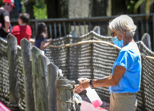 Staff member Kathy Wannemuehler disinfects hand rails as Evansville's Mesker Zoo Park & Botanic Garden opens to the public for the first time since closing due to the coronavirus pandemic Monday, June 15, 2020.