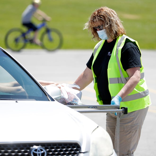Kim Chase, Green Bay Area Public School District food service employee, gives out bagged lunches on Monday, June 15, 2020, during the first day of the summer meal program, which provides a bagged breakfast and lunch for all children Mondays through Fridays.