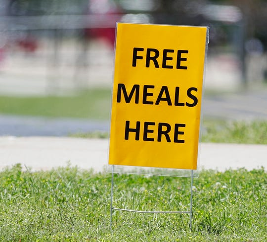 """A """"Free meals here"""" sign is pictured outside Edison Middle School on June 15, 2020, in Green Bay, Wis. Green Bay Area Public School District's summer meals program offers children a drive-through bagged breakfast and lunch Mondays through Fridays."""