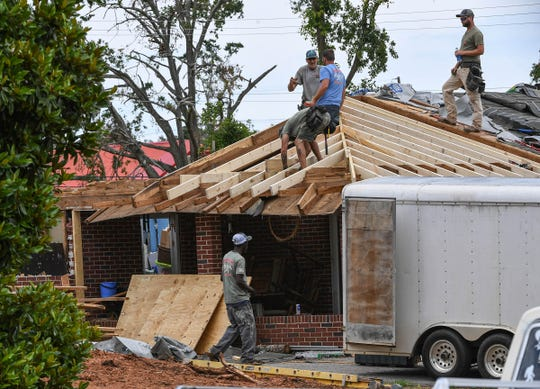 Roofers from Workhorse Roofing repair a home on East South 6th Street in Seneca nearly two months after a tornado damaged many homes and businesses. Repairmen, SCDOT, companies, and individuals are still cleaning up and restoring their city.