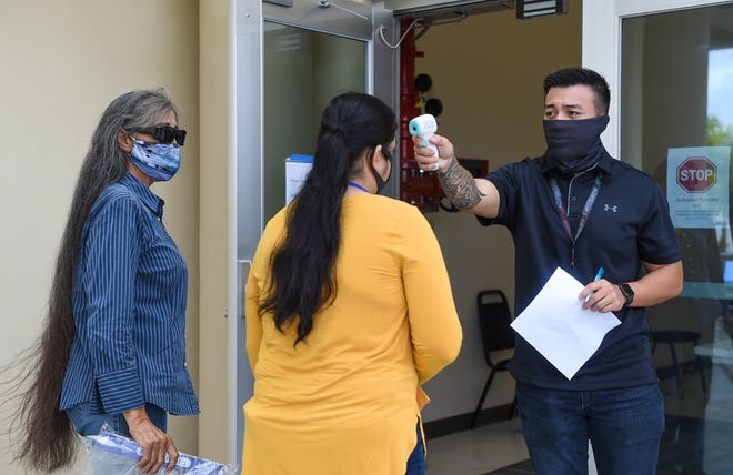 Pandemic Unemployment Assistance staff member Peter John R. Santos Jr. takes the temperature of an applicant outside the PUA Processing Center at Guam Community College in this June 15 file photo.