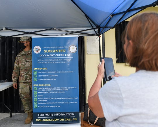 Dededo resident Doris Finona takes a picture of an informational sign outside a Pandemic Unemployment Assistance processing center at the Dededo Branch Public Library, June 15, 2020.
