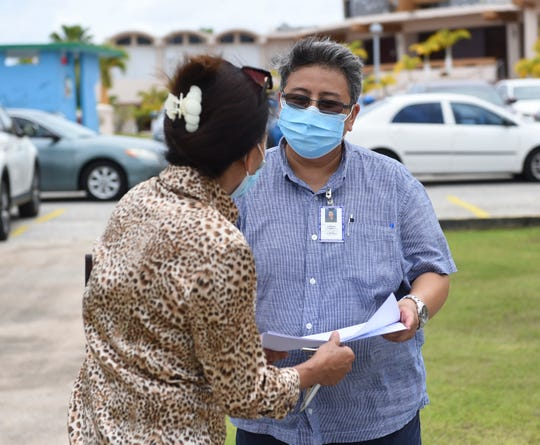 Catherine Q. Cabrera, Guam Public Library System customer service representative, right, assists a resident outside a Pandemic Unemployment Assistance processing center at the Dededo Branch Public Library in this June 15 file photo. While the number of unemploymentclaims climbed to 19,861 as of Thursday, residents continue to await word from the Guam Department of Labor regarding their payments.