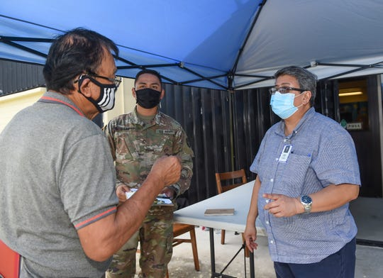 Catherine Q. Cabrera, Guam Public Library System customer service representative, right, informs Yigo resident, Angel M. Fernandez, left, about the Pandemic Unemployment Assistance program's appointment procedure, outside a PUA processing center at the Dededo Branch Public Library, June 15, 2020.