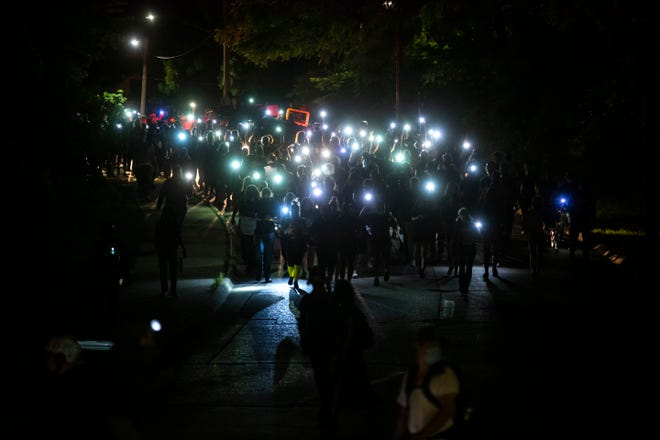 Hundreds of cellphone flash lights illuminate the path for protesters as they make their way towards downtown from the west side of campus during a protest organized by the Iowa Freedom Riders, Sunday, June 14, 2020, in Iowa City, Iowa.