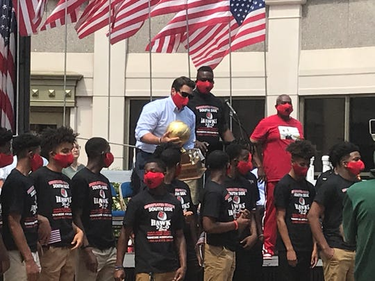 Jackson Mayor Scott Conger presents a gold ball trophy recognizing South Side basketball's undefeated season to members of the team on Sunday.