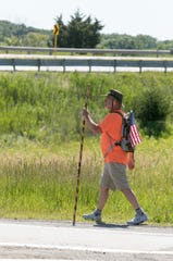 Ed Haass passes the Interstate-96 interchange in Brighton as he walks along Grand River Avenue on his way to Lansing Monday, June 15, 2020.