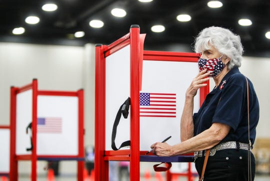 Carol Bothwell wore a patriotic mask she made herself as she voted early at the Kentucky Exposition Center Monday. She said she was initially confused by the sheet of paper listing a withdrawal of candidates from certain races. June 15, 2020