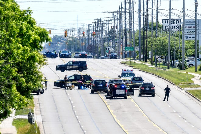 Police investigate the scene of a fatal shooting on Saginaw Highway between Canal and Creyts road on Monday, June 15, 2020, in Delta Township.