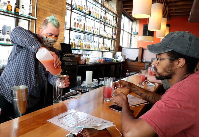 Customer Morgan Williams watches bartender  Adam Esser mix a drink as at Blue Bat Kitchen and Tequilaria, 249 N. Water St. in the Third Ward. The staff wears masks indoors and out at the restaurant and at other Hospitality Democracy restaurants.