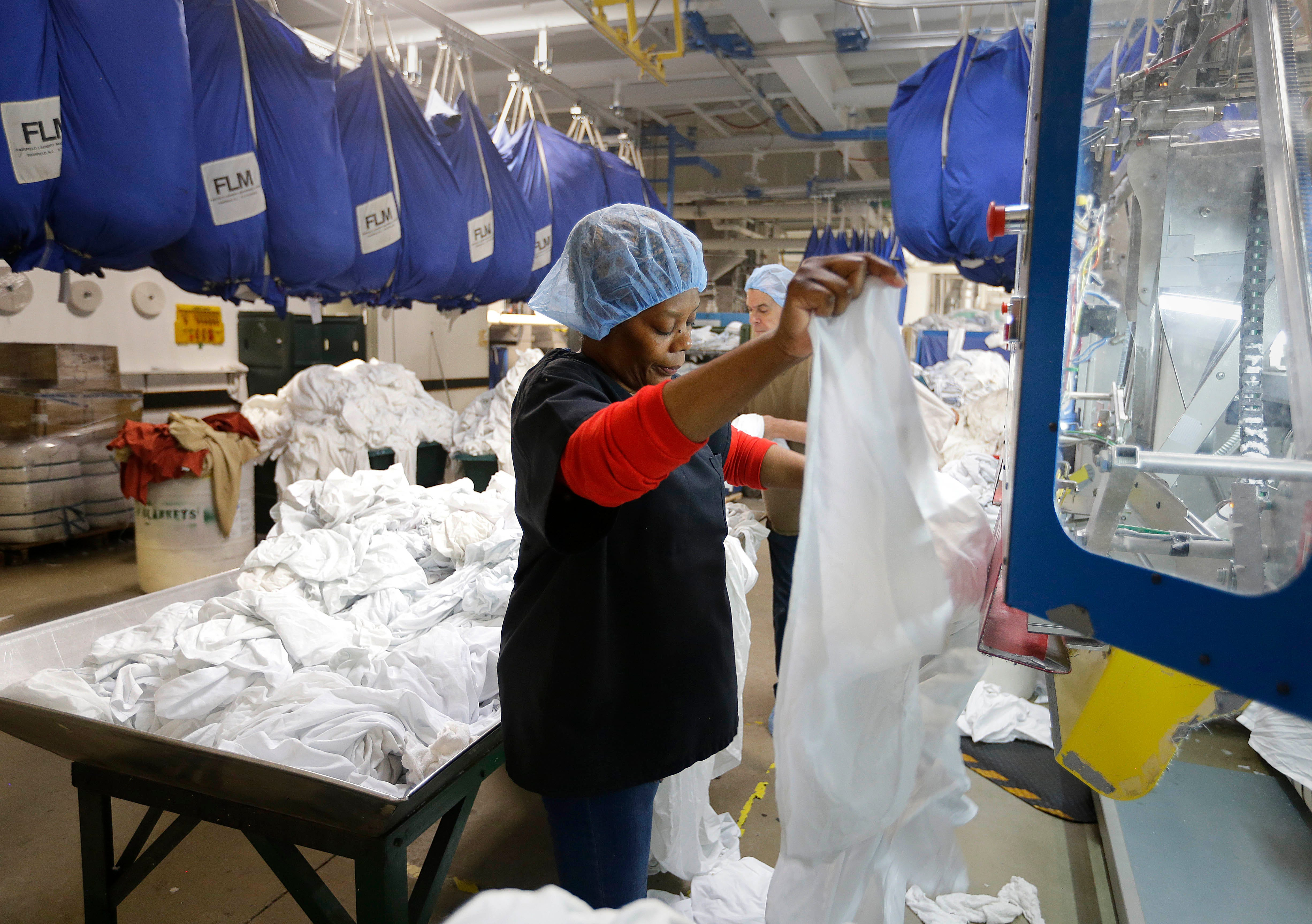 A worker places damp sheets on a drying and folding machine at  The Evergreen Cooperative Laundry in Cleveland.